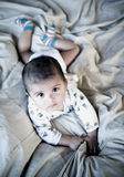 Cute baby. A cute baby lying on the bed, looking up Stock Photography