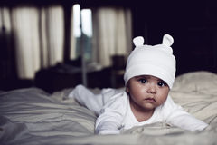Cute baby. With hat lying on a bed Stock Photos