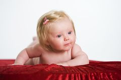 A cute baby. Portrait of a cute blond haired baby girl on a red blanket Stock Photography
