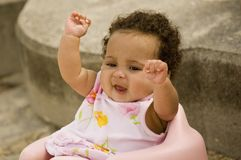 Cute baby. Seated in pink chair, winner expression with hands lifted into the air Stock Photo