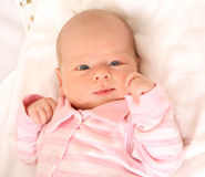 Cute baby. A beautiful caucasian white baby girl head portrait (three months old) with cute facial expression lying on a pink blanket and watching Royalty Free Stock Photography