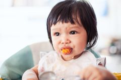 Cute baby asian child girl eating healthy food by herself. And making a mess on her face and hand stock photography