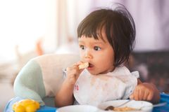 Cute baby asian child girl eating healthy food by herself. And making a mess on her face and hand royalty free stock photography