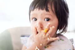 Cute baby asian child girl eating healthy food by herself. And making a mess on her face and hand stock image