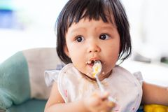 Cute baby asian child girl eating healthy food by herself. And making a mess on her face and hand stock images