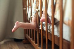 Cute baby bare feet stick out the crib.  Royalty Free Stock Photos