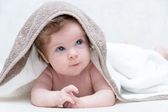 Cute baby after bath, parental care concept. Happy baby having fun. Three-months old baby looking up stock photography