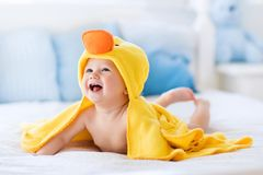Cute baby after bath in yellow duck towel. Happy laughing baby wearing yellow hooded duck towel sitting on parents bed after bath or shower. Clean dry child in royalty free stock photography
