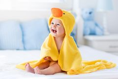 Cute baby after bath in yellow duck towel. Happy laughing baby wearing yellow hooded duck towel sitting on parents bed after bath or shower. Clean dry child in stock photos