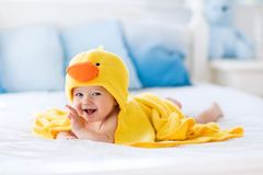 Cute baby after bath in yellow duck towel. Happy laughing baby wearing yellow hooded duck towel sitting on parents bed after bath or shower. Clean dry child in stock image