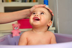 Cute Baby Bathtime. Cute baby is being washed in a purple bathtub by mother Stock Images