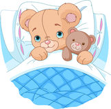 Cute baby bear in bed. Cute baby bear is ready to sleep, hugging his teddy bear Royalty Free Stock Image