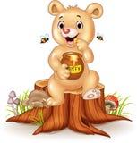 Cute Baby Bear Holding Honey Pot On Tree Stump Stock Photography