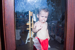 Cute baby behind the glass doors, sad kid Stock Images