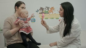 Cute baby being examine by pediatrician with toy stock video footage