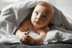 Cute baby with bewildered look sits on spacious bed. Cute baby with bewildered air, blond hair and big light grey eyes sits on spacious soft bed and looks out Royalty Free Stock Image