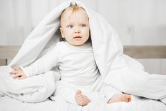 Cute baby with bewildered look sits on spacious bed. Cute baby with bewildered air, blond hair and big light grey eyes sits on spacious soft bed and looks out Stock Photo