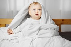 Cute baby with bewildered look sits on spacious bed. Cute baby with bewildered air, blond hair and big light grey eyes sits on spacious soft bed and looks out Stock Image