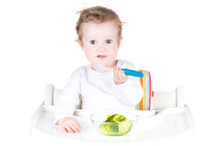 Cute baby with big blue eyes having broccoli for lunch Royalty Free Stock Images