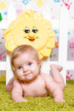 Cute baby with big blue eyes. Cute little baby with big blue eyes  lies down on his stomach, smile and looks towards Royalty Free Stock Image
