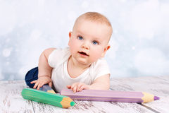 Cute baby with big crayons Royalty Free Stock Photography