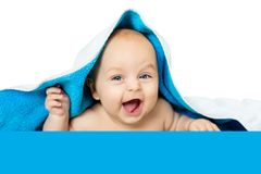Cute baby with big eyes under a blue towel on white, isolated. The child lies on a soft blanket Stock Photos