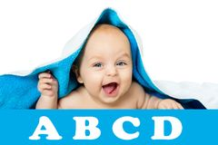 Cute baby with big eyes under a blue towel on white, isolated. The child lies on a soft blanket Stock Photo