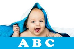 Cute baby with big eyes under a blue towel on white, isolated. The child lies on a soft blanket Stock Images