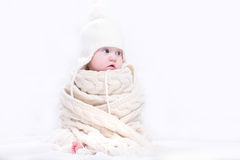Cute baby in a big knitted scarf and hat Royalty Free Stock Photos