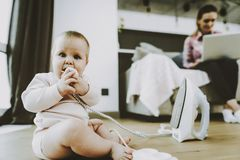 Cute Baby Bites Iron Cord while Mother Networking. Cute Baby Bites Irons Cord while Mother Networking. Portrait of Caucasian Child Sitting on Floor and Holding stock photos