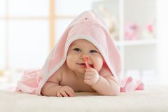 Cute baby biting teether under a hooded towel after bath. Cute baby biting teether toy under pink hooded towel after bathing stock photos