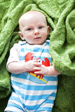 Cute baby on blanket. Cute baby boy in bright summer outfit lying on a green blanket Royalty Free Stock Images