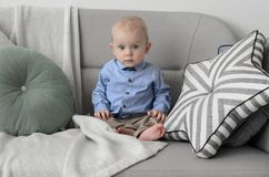 Cute baby with blond hair and blue eyes sitting on the sofa and. Looking at camera royalty free stock photo