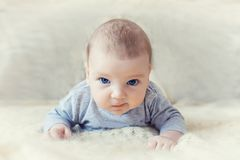 Cute baby with blue eyes crawling forward.  stock photo