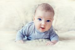 Cute baby with blue eyes crawling forward.  royalty free stock photo