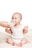 Cute baby with a bottle of milk on a beige blanket Royalty Free Stock Photography