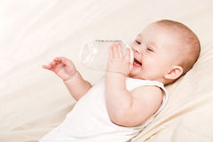 Cute baby with a bottle of milk on a beige blanket Stock Photos
