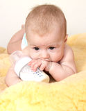 Cute baby with bottle of milk on fur stock image