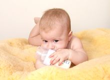 Cute baby with bottle of milk on fur Stock Photos