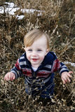 Cute baby boy. Adorable cute caucasian baby toddler boy standing in field looking up into camera Royalty Free Stock Photo