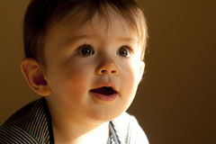 Cute baby boy. Portrait of cute baby boy with sunlight and shadows on face; studio background Stock Photo