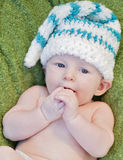 Cute baby boy. Wearing a knit hat holding hands to mouth Royalty Free Stock Photo