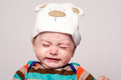Cute baby boy with adorable hat crying. Little child in pain, suffering, teething, refusing and crying. Cute sad baby throwing a tantrum. Baby wants up in the Royalty Free Stock Photography
