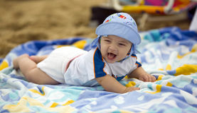 Cute baby boy on a beach towel. Baby boy laughing while laying on a colorful beach towel Stock Images