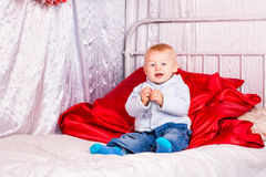 Cute baby boy on a bed playing Royalty Free Stock Photos