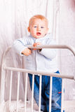 Cute baby boy on a bed playing Royalty Free Stock Photography