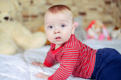 Cute baby boy on a bed trying crawl Royalty Free Stock Images