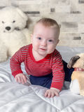 Cute baby boy on bed trying to crawl Royalty Free Stock Image