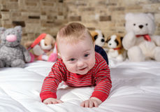 Cute baby boy on bed trying to crawl Royalty Free Stock Photography