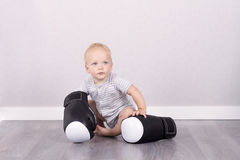 Cute baby boy in boxing gloves against the grey background Royalty Free Stock Image